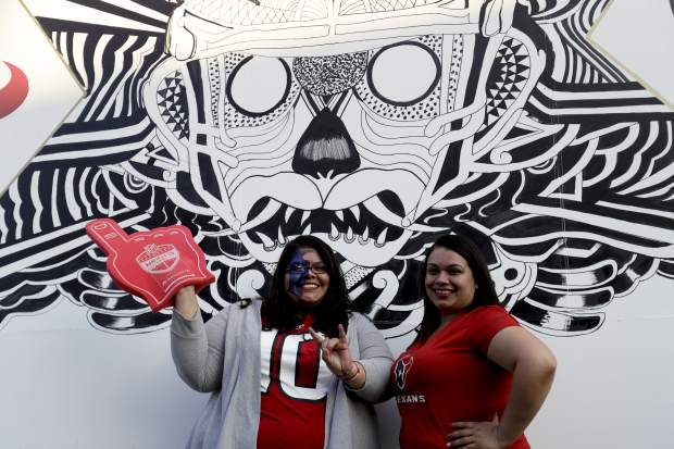 Houston Texans fans pose for a picture outside of Azteca Stadium before an NFL football game between the Houston Texans and the Oakland Raiders Monday, Nov. 21, 2016, in Mexico City. (AP Photo/Rebecca Blackwell)