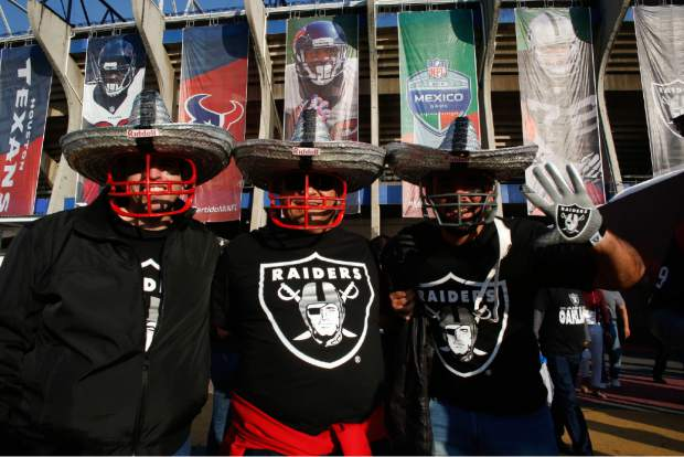 Oakland Raiders fans pose for a picture in front of Azteca Stadium before an NFL football game against the Houston Texans Monday, Nov. 21, 2016, in Mexico City. (AP Photo/Dario Lopez-Mills)