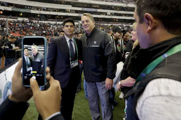 Oakland Raiders head coach Jack Del Rio poses for a picture with members of his Jack Del Rio Foundation before an NFL football game against the Houston Texans Monday, Nov. 21, 2016, in Mexico City. (AP Photo/Eduardo Verdugo)