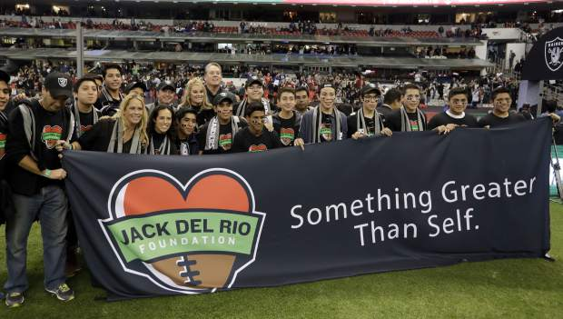 Oakland Raiders head coach Jack Del Rio poses with members of his Jack Del Rio Foundation before an NFL football game against the Houston Texans Monday, Nov. 21, 2016, in Mexico City. (AP Photo/Eduardo Verdugo)