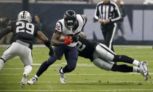 Houston Texans running back Lamar Miller is hauled down by Oakland Raiders defensive end Khalil Mack, right, during the first half of an NFL football game Monday, Nov. 21, 2016, in Mexico City. (AP Photo/Eduardo Verdugo)