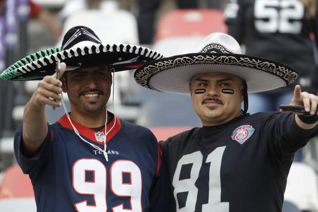 Fans for the Houston Texans and Oakland Raiders look on before an NFL football game Monday, Nov. 21, 2016, in Mexico City. (AP Photo/Rebecca Blackwell)