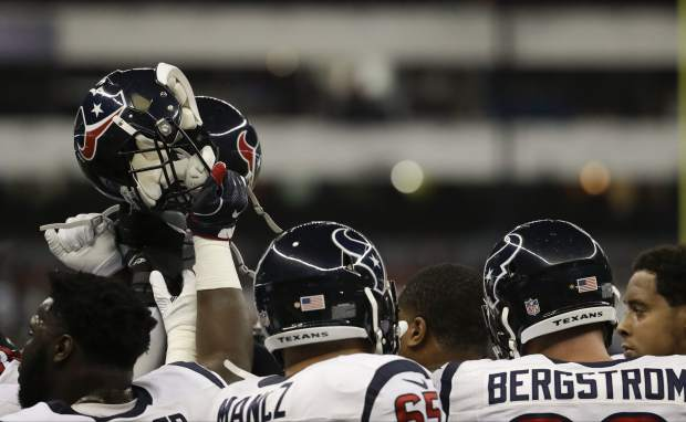 Players from the Houston Texans raise helmets before an NFL football game against the Oakland Raiders Monday, Nov. 21, 2016, in Mexico City. (AP Photo/Rebecca Blackwell)