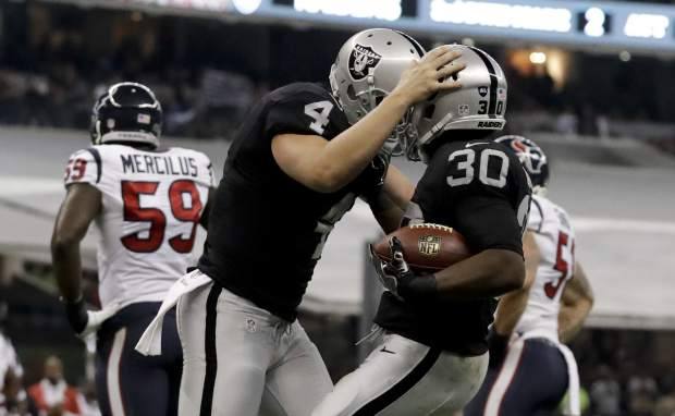 Oakland Raiders running back Jalen Richard, right, celebrates with teammate quarterback Derek Carr after scoring a touchdown during the first half of an NFL football game against the Houston Texans Monday, Nov. 21, 2016, in Mexico City. (AP Photo/Rebecca Blackwell)