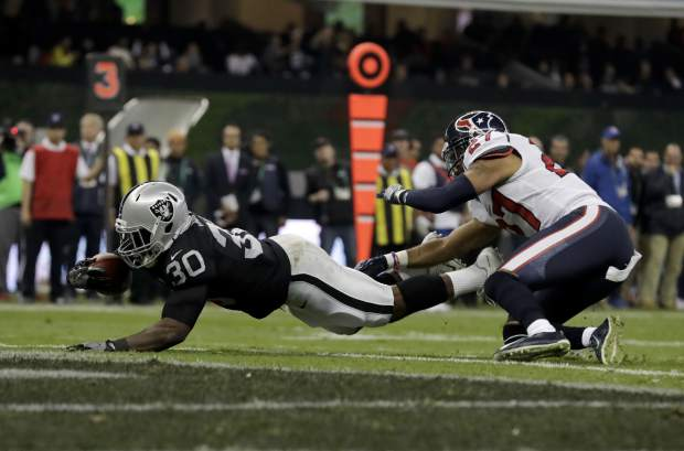 Oakland Raiders running back Jalen Richard scores a touchdown past Houston Texans strong safety Quintin Demps (27) during the first half of an NFL football game Monday, Nov. 21, 2016, in Mexico City. (AP Photo/Rebecca Blackwell)