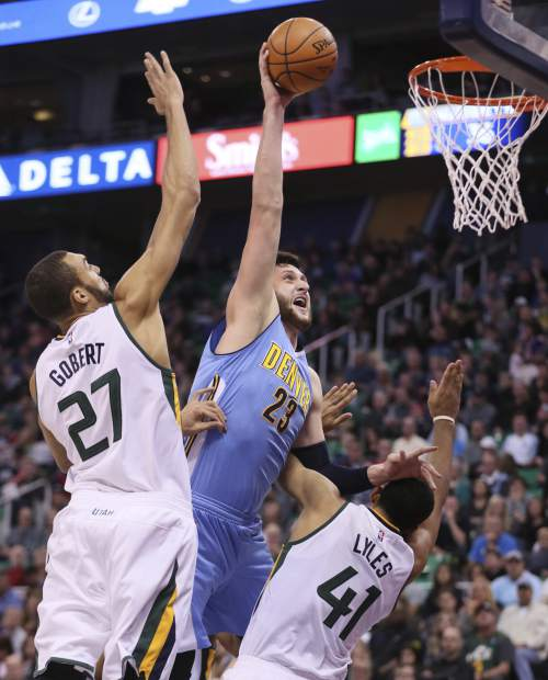 Denver Nuggets center Jusuf Nurkic (23), dunks the ball over Utah Jazz center Rudy Gobert (27) and Utah Jazz forward Trey Lyles (41), during the first half of an NBA basketball game against the , Wednesday, Nov. 23, 2016, in Salt Lake City. (AP Photo/George Frey)