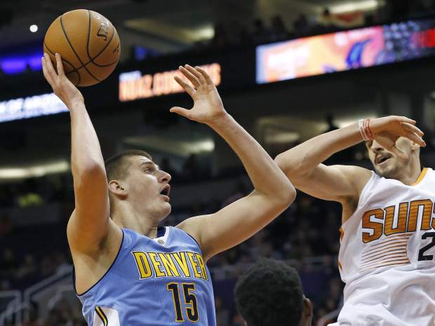 Denver Nuggets forward Nikola Jokic (15) goes up to shoot against Phoenix Suns center Alex Len, right, during the first half of an NBA basketball game Sunday, Nov. 27, 2016, in Phoenix. (AP Photo/Ross D. Franklin)