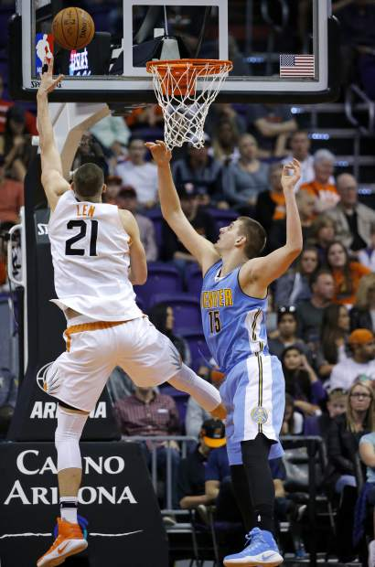 Phoenix Suns center Alex Len (21) gets a shot off over Denver Nuggets forward Nikola Jokic (15) during the first half of an NBA basketball game Sunday, Nov. 27, 2016, in Phoenix. (AP Photo/Ross D. Franklin)
