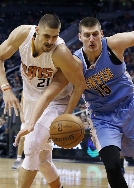 Denver Nuggets forward Nikola Jokic (15) battles with Phoenix Suns center Alex Len (21) for a loose ball during the second half of an NBA basketball game Sunday, Nov. 27, 2016, in Phoenix. The Nuggets defeated the Suns 120-114. (AP Photo/Ross D. Franklin)
