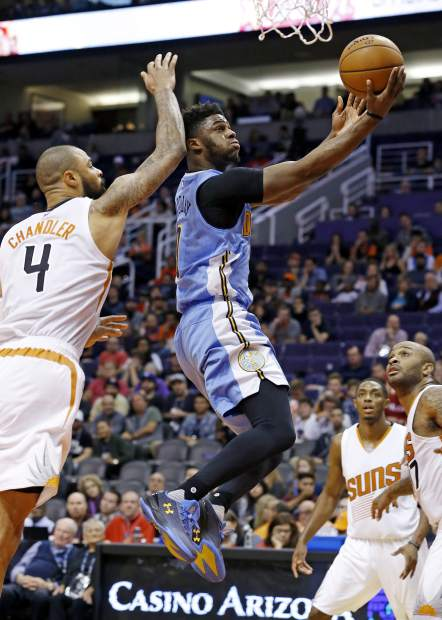 Denver Nuggets guard Emmanuel Mudiay, second from left, drives past Phoenix Suns center Tyson Chandler (4) as Suns guard Brandon Knight and forward P.J. Tucker, right, watch during the first half of an NBA basketball game Sunday, Nov. 27, 2016, in Phoenix. (AP Photo/Ross D. Franklin)