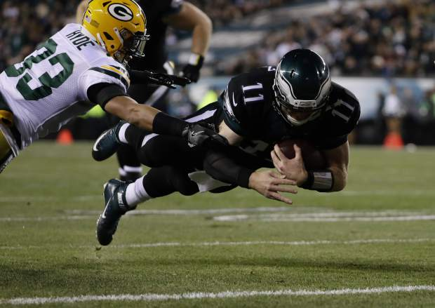 Philadelphia Eagles' Carson Wentz (11) dives for a touchdown past Green Bay Packers' Micah Hyde (33) during the first half of an NFL football game against the Green Bay Packers, Monday, Nov. 28, 2016, in Philadelphia. (AP Photo/Michael Perez)