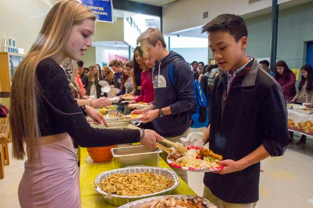 Roaring Fork High School Senior Kristin Page serves food to freshman Shaun Teitler during the school's Thanksgiving meal on Friday.