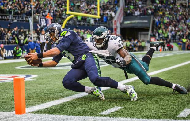 Seattle Seahawks quarterback Russell Wilson reaches for the end zone, scoring on a pass from wide receiver Doug Baldwin, past Philadelphia linebacker Nigel Bradham in the third quarter of an NFL football game in Seattle on Sunday, Nov. 20, 2016. Wilson became the first quarterback in franchise history to catch a touchdown, a perfect end-around pass from Baldwin to Seattle's athletic QB as he ran down the left sideline and dove into the end zone to give the Seahawks a 23-7 lead. (Dean Rutz/The Seattle Times via AP)