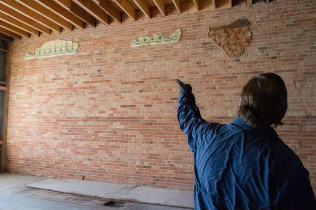 Steve Davis points out some of the old wallpaper that was revealed when the walls were stripped to the original brick.
