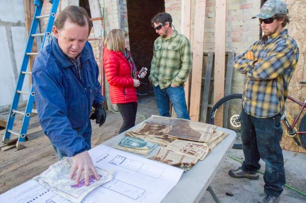 Steve Davis looks over relics found in the walls of the 719 Grand Ave. building that he and wife Marilyn and sons Ryan, center, and Michael are in the midst of renovating in downtown Glenwood Springs.