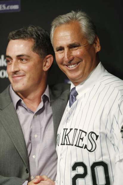 Newly-named Colorado Rockies manager Bud Black, right, poses for photographers after pulling on his new jersey along with general manager Jeff Bridich during a news conference to introduce Black as the new skipper on Monday, Nov. 7, 2016, in Denver. Black succeeds Walt Weiss, who left after four seasons as manager at the conclusion of the regular season. (AP Photo/David Zalubowski)