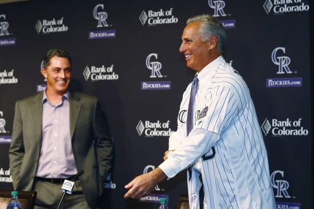 Newly-named Colorado Rockies manager Bud Black pulls on his new jersey as general manager Jeff Bridich, left, looks on during a news conference to introduce him as the new skipper on Monday, Nov. 7, 2016, in Denver. Black succeeds Walt Weiss, who left after four seasons as manager at the conclusion of the regular season. (AP Photo/David Zalubowski)