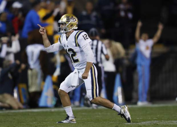UCLA quarterback Mike Fafaul turns to his team's bench after throwing a touchdown pass to wide receiver Darren Andrews against Colorado during the first half of an NCAA college football game Thursday, Nov. 3, 2016, in Boulder, Colo. (AP Photo/David Zalubowski)