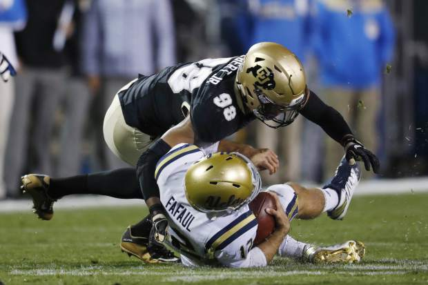 Colorado linebacker Jimmie Gilbert, top, hits UCLA quarterback Mike Fafaul during the first half of an NCAA college football game Thursday, Nov. 3, 2016, in Boulder, Colo. (AP Photo/David Zalubowski)