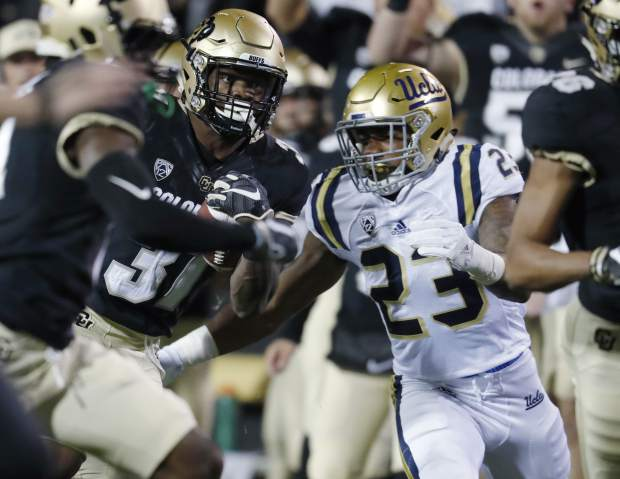Colorado linebacker Kenneth Olugbode, left, is tackled by UCLA running back Nate Starks after an interception during the first half of an NCAA  college football game Thursday, Nov. 3, 2016, in Boulder, Colo. (AP Photo/David Zalubowski)