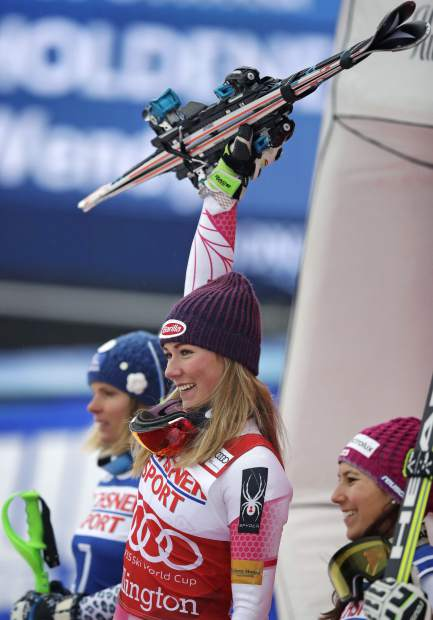 Mikaela Shiffrin, of the United States, center, raises her skis as she celebrates her first place in the alpine skiing women's World Cup slalom in Killington, Vt., Sunday, Nov. 27, 2016. With Shiffrin are second place winner Veronika Velez Zuzulova, of Slovenia, left, and third place winner Wendy Holdener, of Switzerland, right. (AP Photo/Charles Krupa)