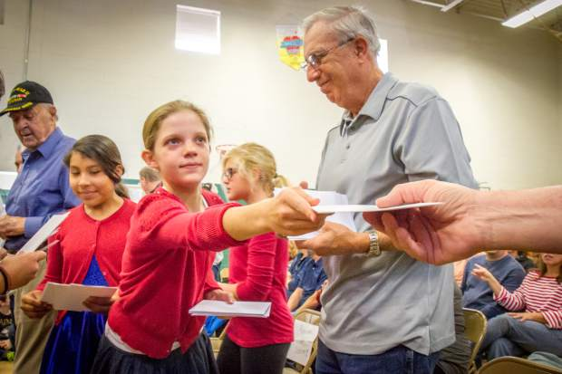 Sopris Elementary student Madison Stewart passes out letters to veterans during the concert put on by fourth- and fifth-graders to honor veterans of the community in celebration and remembrance of Veterans Day.