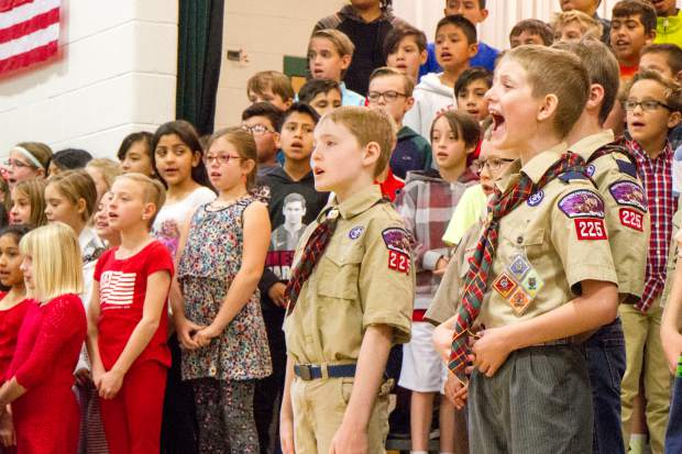 Sopris Elementary School student Tanner Merritt, right, along with other fourth- and fifth-graders as well as members of Boy Scout Troop 225, take part in the concert to honor veterans of the community in a celebration and remembrance of Veterans Day on Thursday morning at the School.