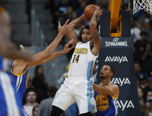 Denver Nuggets guard Gary Harris, center, looks to pass as Golden State Warriors center JaVale McGee, left, and guard Stephen Curry defend in the first half of an NBA basketball game Thursday, Nov. 10, 2016, in Denver. (AP Photo/David Zalubowski)