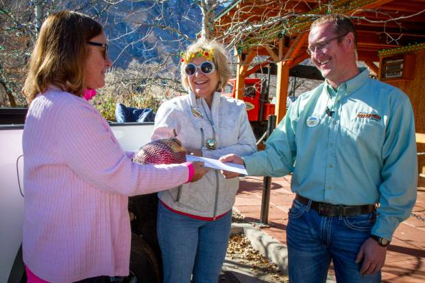 Karen Lang (left) hands her turkey over to Corinne Diemoz and tram manager Derek Bihr during the third annual Turkey Tram-A-Ganza on Saturday. The Glenwood Caverns Adventure Park teamed up with KSNO and Big Horn Toyota for this year's Turkey Tram-A-Ganza to benefit Lift-Up. People were invited to bring a frozen turkey in exchange for up to four free tram passes to be used that day for the kick-off of the Winter on the Mountain party. For more information on upcoming Winter on the Mountain events go to glenwoodcaverns.com