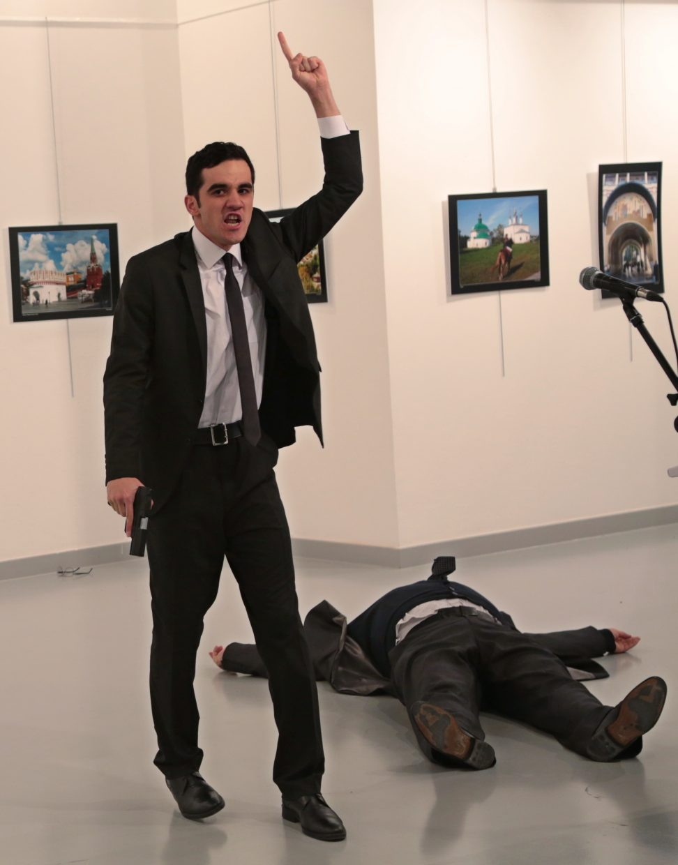 A man gestures after shooting Andrei Karlov, the Russian Ambassador to Turkey, on the floor, at a photo gallery in Ankara, Turkey, Monday, Dec. 19, 2016. The ambassador's condition wasn't immediately known.