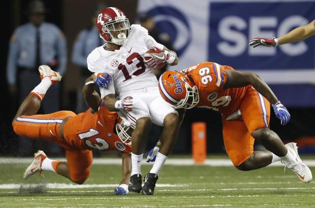 Alabama wide receiver ArDarius Stewart (13) is hit by Florida defensive lineman Jachai Polite (99) and Florida linebacker Daniel McMillian (13) during the second half of the Southeastern Conference championship NCAA college football game, Saturday, Dec. 3, 2016, in Atlanta.(AP Photo/John Bazemore)