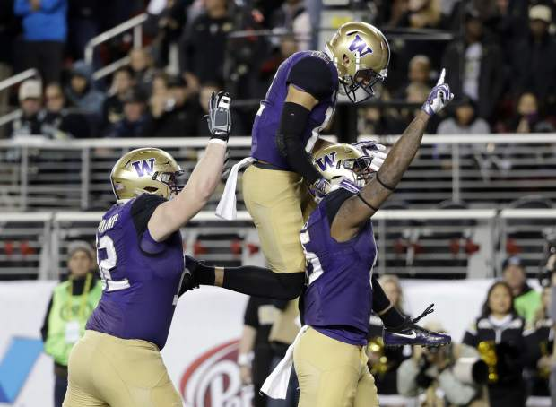 FILE - In this Friday, Dec. 2, 2016, file photo, Washington tight end Darrell Daniels, right, celebrates his touchdown catch with teammates Aaron Fuller, center, and Jake Eldrenkamp during the first half of the Pac-12 Conference championship NCAA college football game against Colorado in Santa Clara, Calif. Alabama will play Washington and Ohio State is set to face Clemson in the College Football Playoff semifinals, announced Sunday, Dec. 4. (AP Photo/Marcio Jose Sanchez)