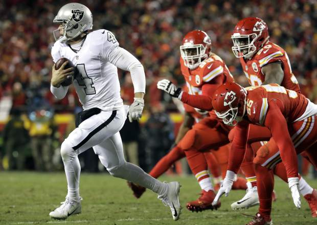 Oakland Raiders quarterback Derek Carr (4) runs away from Kansas City Chiefs linebacker Dee Ford (55), defensive lineman Rakeem Nunez-Roches (99) and linebacker Justin Houston (50) during the first half of an NFL football game in Kansas City, Mo., Thursday, Dec. 8, 2016. (AP Photo/Charlie Riedel)