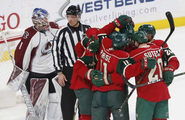 Minnesota Wild players congratulate Charlie Coyle after Coyle's power play goal against Colorado Avalanche goalie Semyon Varlamov, left, of Russia during the first period of an NHL hockey game Tuesday, Dec. 20, 2016, in St. Paul, Minn. (AP Photo/Jim Mone)