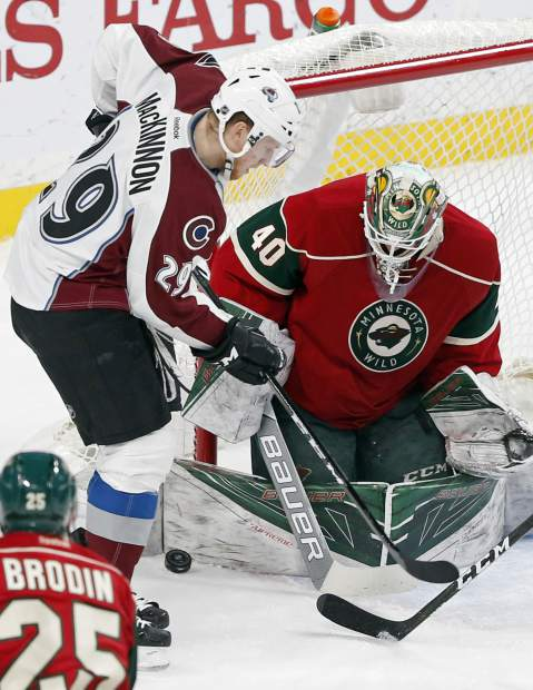 Minnesota Wild goalie Devan Dubnyk, right, blocks a scoring threat by Colorado Avalanche's Nathan MacKinnon during the second period of an NHL hockey game Tuesday, Dec. 20, 2016, in St. Paul, Minn. (AP Photo/Jim Mone)