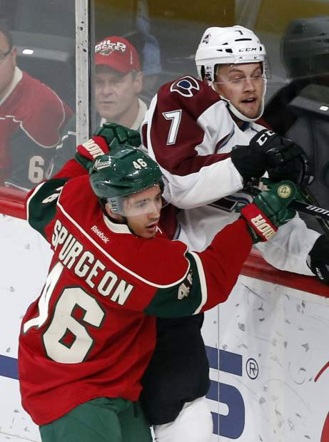Minnesota Wild's Jared Spurgeon, left, pins Colorado Avalanche's John Mitchell to the boards during the first period of an NHL hockey game Tuesday, Dec. 20, 2016, in St. Paul, Minn. (AP Photo/Jim Mone)