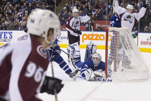 Colorado Avalanche centre Matt Duchene, center, and Colorado Avalanche centre Nathan MacKinnon, right, celebrate as Colorado Avalanche right wing Mikko Rantanen, left, scores on Toronto Maple Leafs goaltender Antoine Bibeau during first period NHL hockey action in Toronto, on Sunday, Dec. 11, 2016. (Chris Young/The Canadian Press via AP)