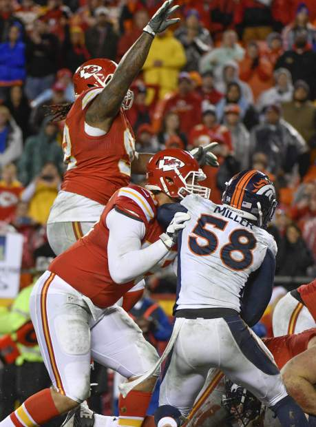 In this Sunday, Dec. 25, 2016 photo, Kansas City Chiefs defensive lineman Dontari Poe, top left, who lined up as quarterback, throws a touchdown pass to tight end Demetrius Harris, as Chiefs offensive lineman Jah Reid (75) blocks Denver Broncos linebacker Von Miller (58) during the second half of an NFL football game Kansas City. (AP Photo/Ed Zurga)