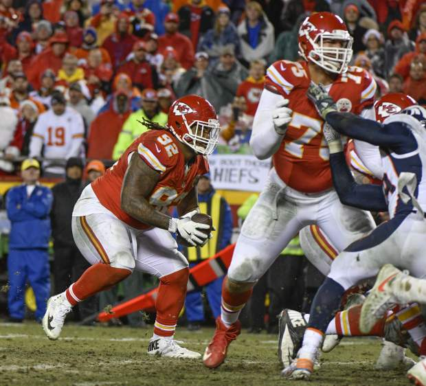 In this Sunday, Dec. 25, 2016 photo, Kansas City Chiefs defensive lineman Dontari Poe (92) takes a snap as quarterback as offensive lineman Jah Reid (75) blocks Denver Broncos linebacker Von Miller, far right, during the second half of an NFL football game in Kansas City, Mo. Poe threw a touchdown pass to tight end Demetrius Harris (AP Photo/Ed Zurga)