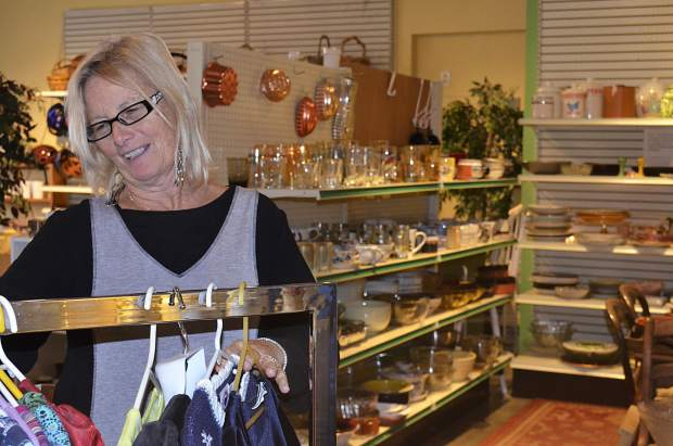 Rhonda Bell, manager at Defiance Thrift Store in Glenwood Springs, racks new clothing as holiday shoppers pick over the store's inventory.