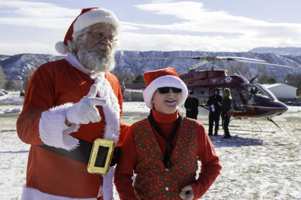 Eleven-year-old Matthew Rhine tells Santa what he wants for Christmas at the E. Dene Moore Care Center in Rifle on Saturday. Santa and two of his elves were flown to the care center by the Classic Air Medical team on Saturday afternoon to make a special visit to the residents and give kids a chance to express what they wanted for Christmas.