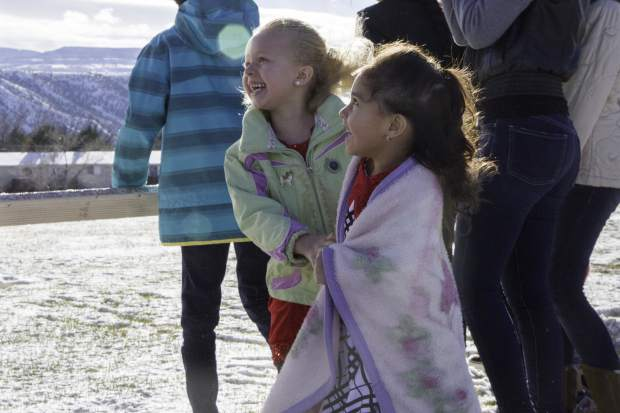 Friends McKinley Melendez, left, and Abril Molinda, 4, jump in excitement at the arrival of Santa and two of his elves who were flown to the E. Dene Moore Care Center in Rifle by the Classic Air Medical helicopter on Saturday afternoon.
