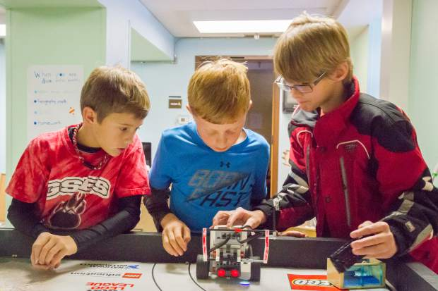 From left, Glenwood Springs Elementary School fourth-graders Jacob Roggie, Benny Swanson and Ezra Goscha work on the Lego robot they put together and will be using at the First Lego League state tournament in Denver.