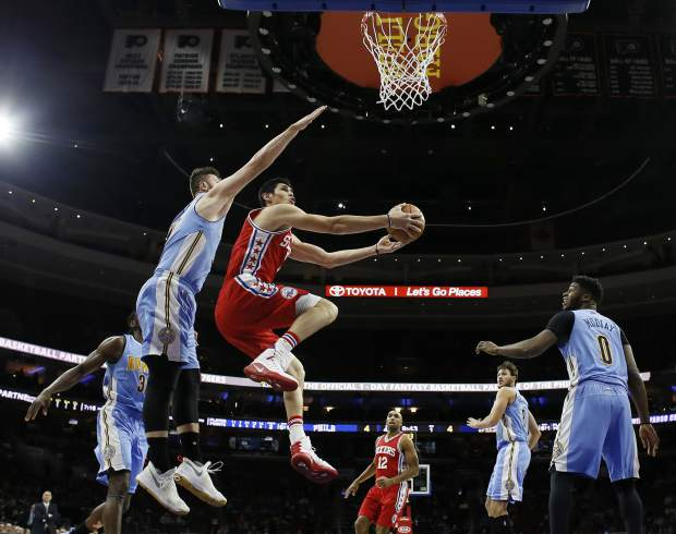 Philadelphia 76ers' Ersan Ilyasova, center, goes up for a shot against Denver Nuggets' Jusuf Nurkic, left, as Emmanuel Mudiay looks on during the first half of an NBA basketball game, Monday, Dec. 5, 2016, in Philadelphia. (AP Photo/Matt Slocum)