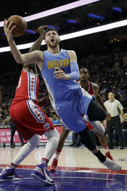 Denver Nuggets' Jusuf Nurkic, right, goes up for a shot past Philadelphia 76ers' Joel Embiid during the first half of an NBA basketball game, Monday, Dec. 5, 2016, in Philadelphia. (AP Photo/Matt Slocum)