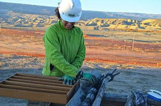 USGS scientist Sarah Hawkins, lead scientist for the Mancos Shale assessment, examines a core drilled for the study she led.
