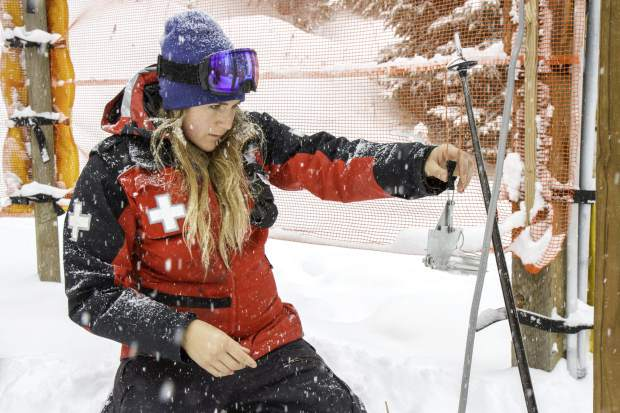 Rachel Thomas checks the density and temperature of the snow after a morning of heavy snowfall. Checking the density gives the crews a better idea of the condition and stability of the snow on the slopes.
