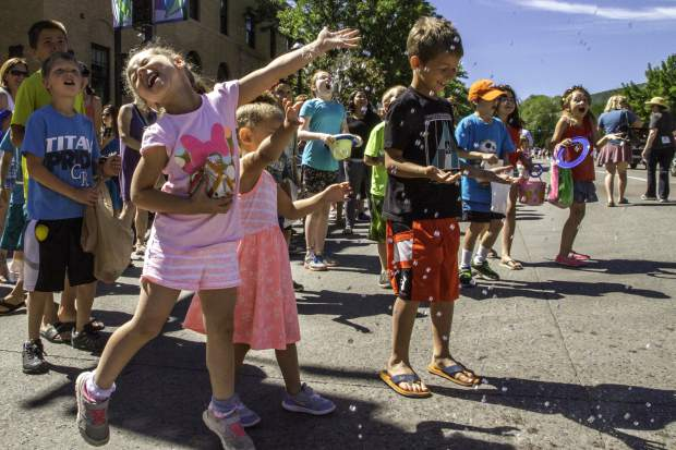 Kids enjoyed being sprayed with water during a hot June morning in downtown Glenwood Springs for the 119th Annual Strawberry Days Parade.