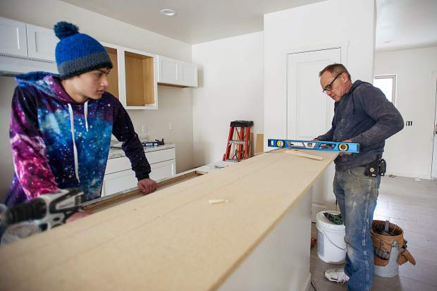Mike Pazzin and his son Dustin work on the kitchen counters in Jamie Wilson's new Habitat for Humanity home in Carbondale on Wednesday.