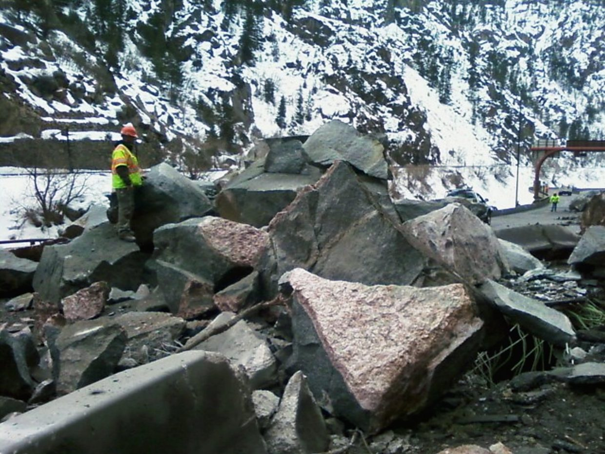 A worker with the Colorado Department of Transportation stands by boulders that crashed down in March 2010 near the Hanging Valley Tunnel in Glenwood Canyon.